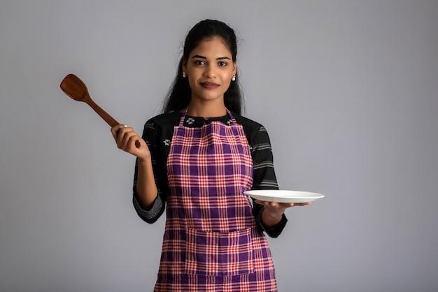 Młoda dziewczyna trzyma i pozowanie z łopatką naczynia kuchenne i talerz na szaro