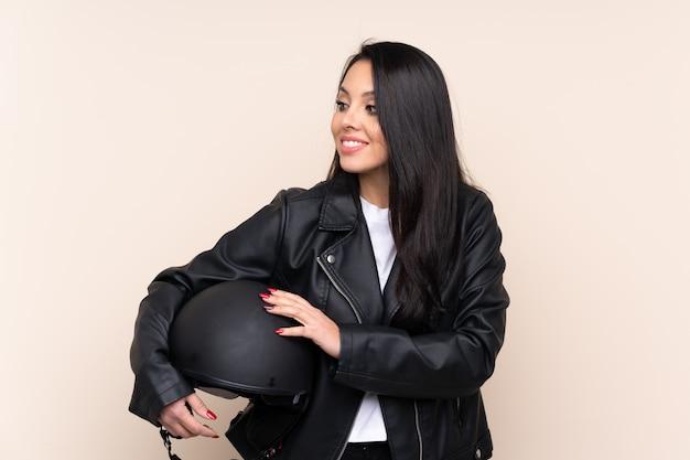 Młoda dziewczyna trzyma kask motocyklowy na ścianie śmiejąc się