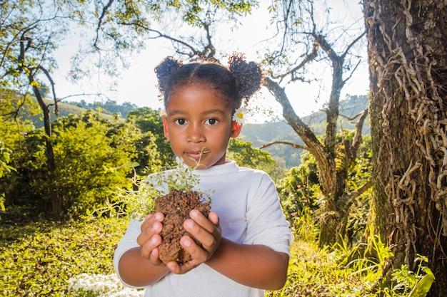 Młoda dziewczyna trzyma kawałek gleby