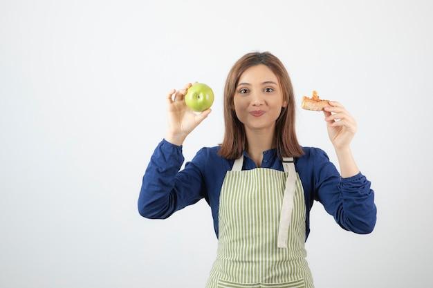 Młoda dziewczyna trzyma kawałek pizzy i jabłka na białej ścianie.