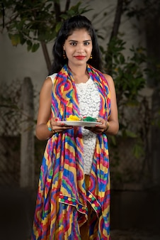 Młoda dziewczyna trzyma kolory proszku w talerzu na festiwalu kolorów o nazwie holi