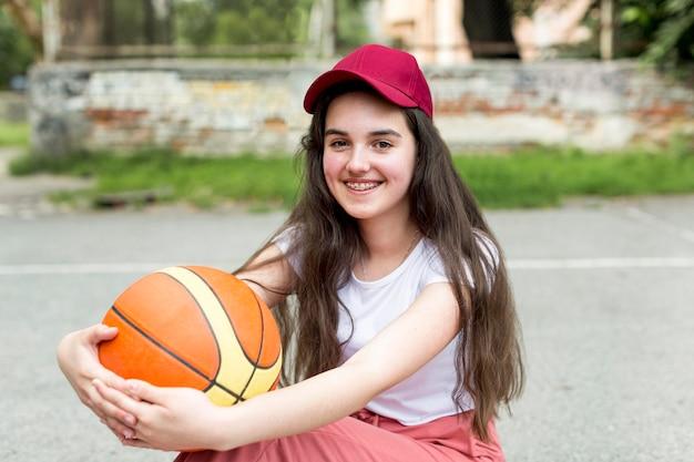 Młoda dziewczyna trzyma koszykówkę w jej amrs