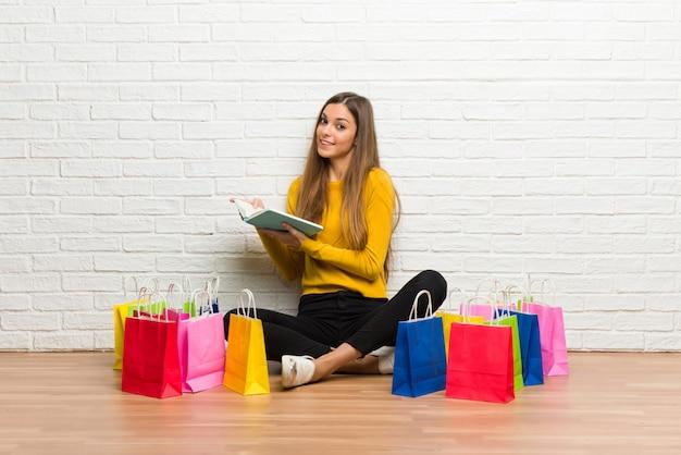 Młoda dziewczyna trzyma książkę i cieszy się czytanie z udziałem torba na zakupy