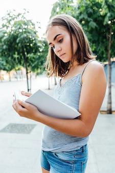 Młoda dziewczyna trzyma książkę na ulicy
