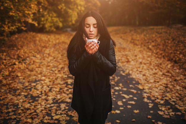Młoda dziewczyna trzyma kubek gorącego napoju i uśmiecha się na tle lasu jesienią