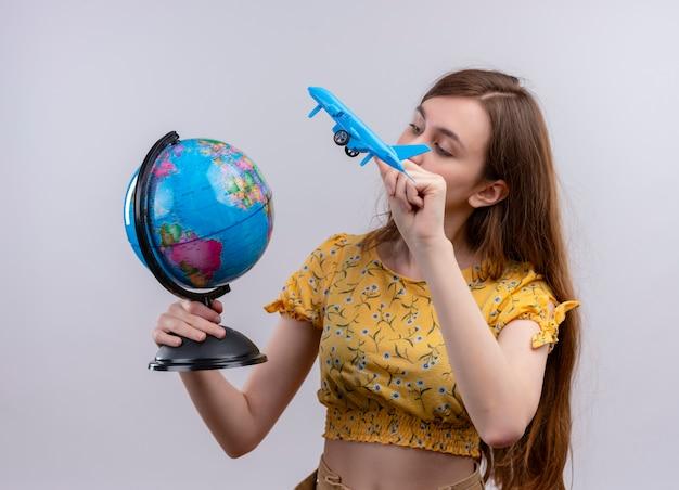 Młoda dziewczyna trzyma kulę ziemską i model samolotu i patrząc na kulę ziemską na odizolowanej białej ścianie