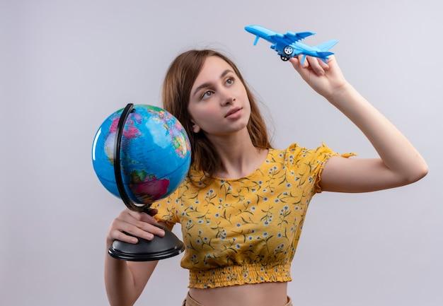 Młoda dziewczyna trzyma kulę ziemską i model samolotu i patrząc na model samolotu na odizolowanej białej ścianie