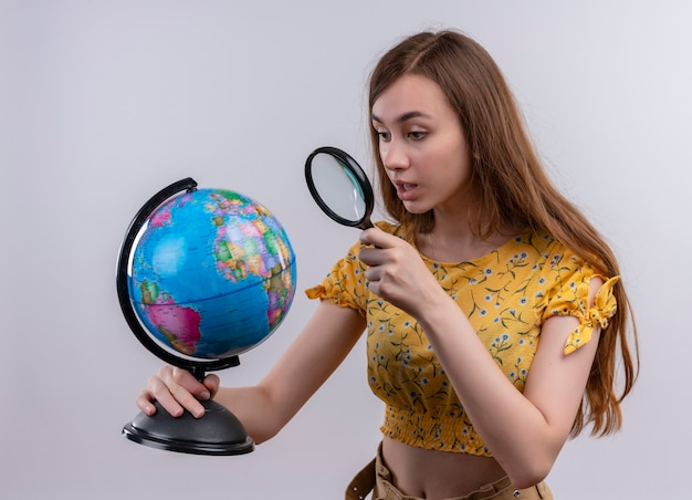 Młoda dziewczyna trzyma kulę ziemską i patrząc przez szkło powiększające na nią na odizolowanej białej ścianie