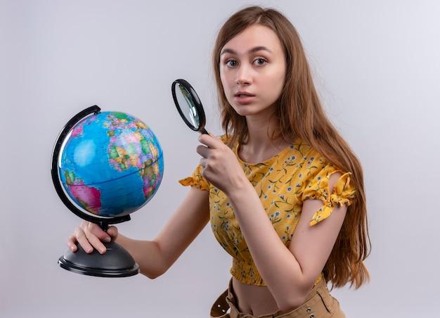 Młoda dziewczyna trzyma kulę ziemską i szkło powiększające patrząc na na białym tle białej ścianie