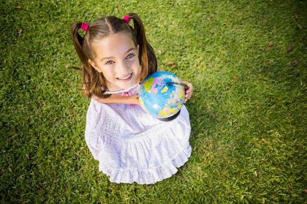 Młoda dziewczyna trzyma kulę ziemską