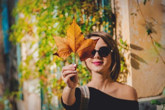Młoda dziewczyna trzyma liść w okularach przeciwsłonecznych