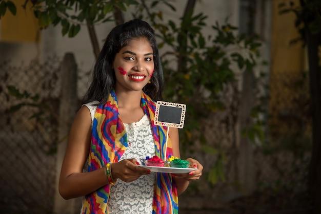 Młoda dziewczyna trzyma małą deskę i pudrowany kolor z okazji festiwalu holi.