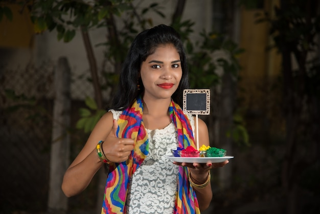 Młoda dziewczyna trzyma małą deskę i sproszkowany kolor z okazji festiwalu holi.