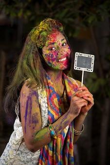 Młoda dziewczyna trzyma małą deskę z okazji festiwalu holi