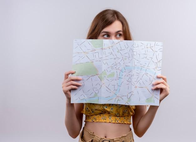Młoda dziewczyna trzyma mapę, chowając się za nią i patrząc na prawą stronę na na białym tle białej ściany z miejsca na kopię