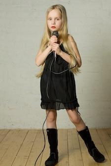 Młoda dziewczyna trzyma mikrofon - piosenkarka rockowa