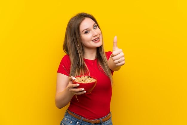 Młoda dziewczyna trzyma miskę płatków z kciukami do góry, ponieważ stało się coś dobrego