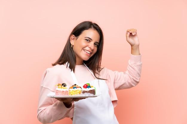 Młoda dziewczyna trzyma mnóstwo różnych mini ciasta nad izolowaną ścianą świętuje zwycięstwo