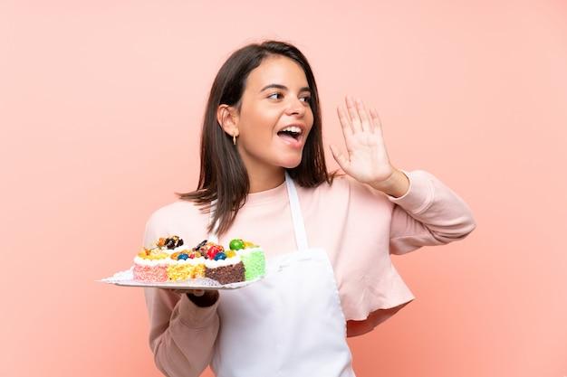 Młoda dziewczyna trzyma mnóstwo różnych mini ciastka nad odosobnioną ścianą krzyczy z usta szeroko otwarty