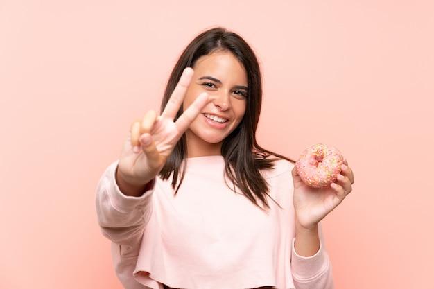 Młoda dziewczyna trzyma pączek nad odosobnioną menchii ścianą uśmiecha się zwycięstwo znaka i pokazuje