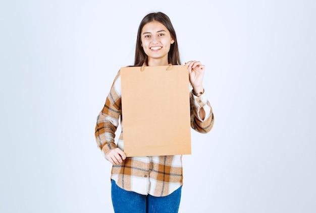 Młoda dziewczyna trzyma pakiet rzemiosła papieru i stojąc nad białą ścianą.