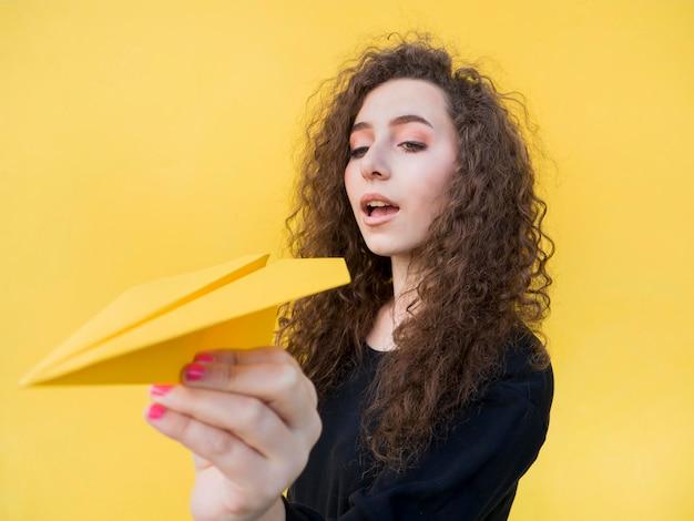 Młoda dziewczyna trzyma papierowego samolot