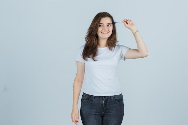 Młoda dziewczyna trzyma pióro na głowie w t-shirt, dżinsy i patrząc radośnie. przedni widok.