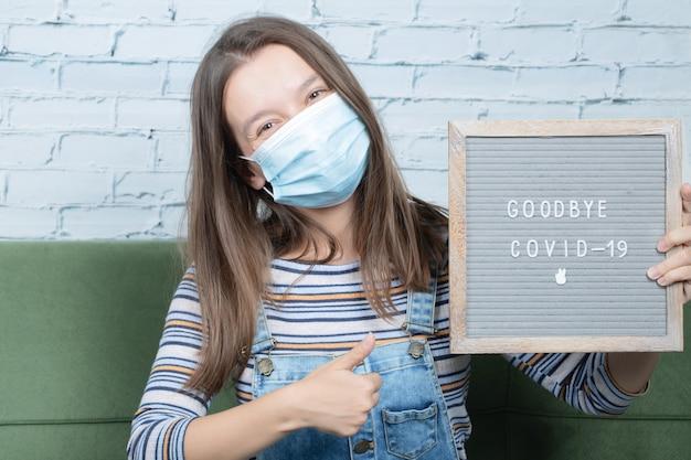 Młoda dziewczyna trzyma plakat przeciwko covid i pandemy
