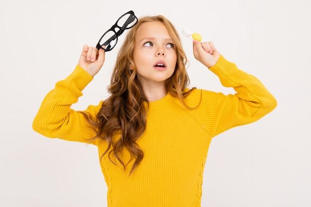 Młoda dziewczyna trzyma pojemnik na soczewki i okulary w ręku