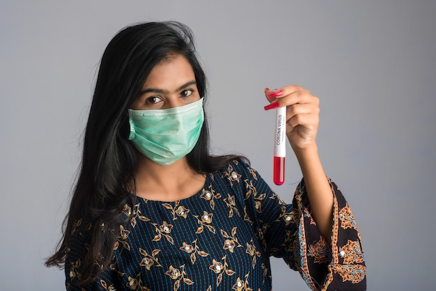 Młoda dziewczyna trzyma probówkę z próbką krwi do koronawirusa lub analizy 2019-ncov.