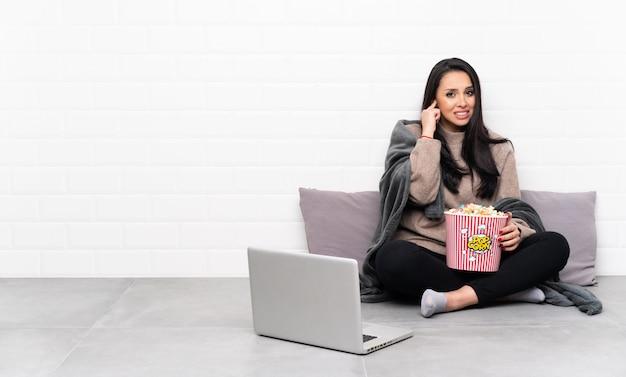 Młoda dziewczyna trzyma puchar popcorns i pokazuje film w laptopie udaremniającym i zakrywającym ucho