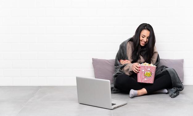 Młoda dziewczyna trzyma puchar popcorns i pokazuje film w laptopie uśmiecha się dużo