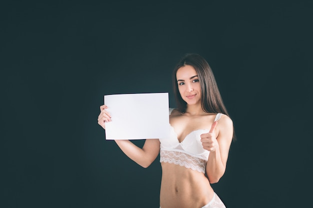 Młoda dziewczyna trzyma pustego sztandar. młoda kobieta z długimi czarnymi włosami stojakami odizolowywającymi na czerni ścianie. dziewczyna ma sportową figurę, jest ubrana w białą bieliznę. piękne figi i stanik.