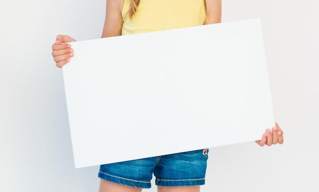 Młoda dziewczyna trzyma pusty plakat