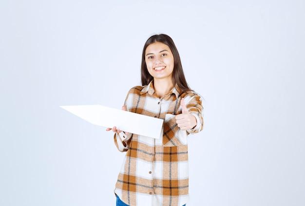 Młoda dziewczyna trzyma pusty wskaźnik strzałki mowy i daje kciuk w górę.