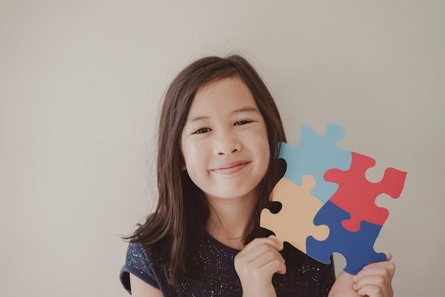 Młoda dziewczyna trzyma puzzle układanki, zdrowie psychiczne dziecka, światowy dzień świadomości autyzmu