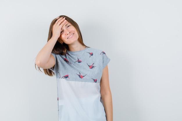 Młoda dziewczyna trzyma rękę na czole w t-shirt i patrząc wesoły, widok z przodu.