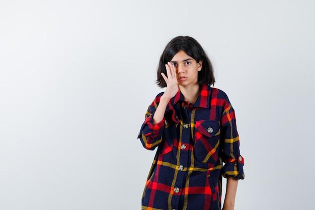 Młoda dziewczyna trzyma rękę w pobliżu ust, próbuje zadzwonić do kogoś w kraciastej koszuli i wygląda poważnie, widok z przodu.