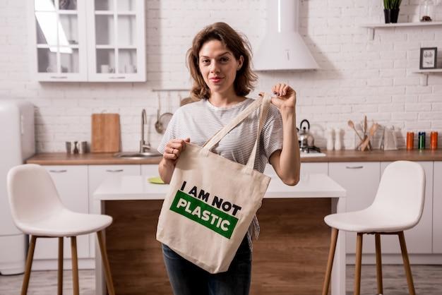 Młoda dziewczyna trzyma sukienną torbę. w kuchni nie jestem plastykiem.