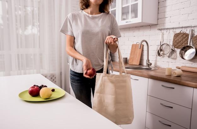 Młoda dziewczyna trzyma sukienną torbę. w kuchni