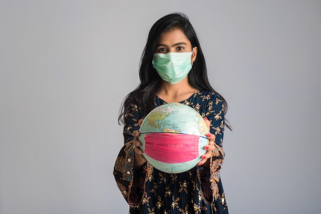 Młoda dziewczyna trzyma światową kulę ziemską z medycyny twarzy maską. światowa epidemia koronawirusa.