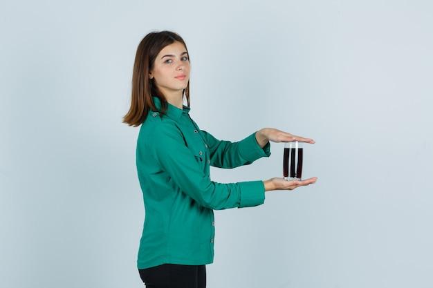 Młoda dziewczyna trzyma szklankę czarnego płynu w obu rękach, patrząc przez ramię w zieloną bluzkę, czarne spodnie i patrząc wesoło, widok z przodu.