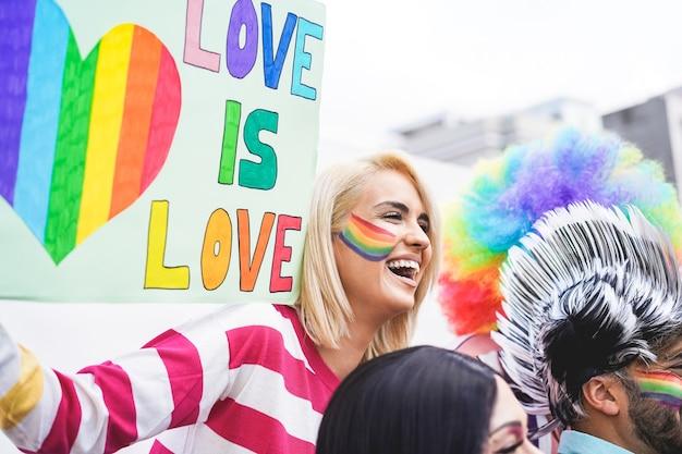 Młoda dziewczyna trzyma sztandar miłość jest miłością na paradzie dumy gejowskiej