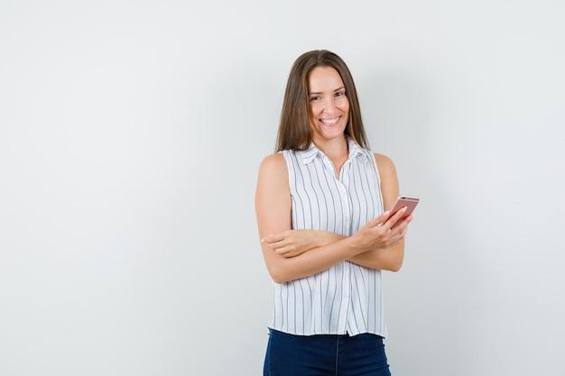 Młoda dziewczyna trzyma telefon komórkowy w t-shirt, dżinsy i patrząc wesoło, widok z przodu.