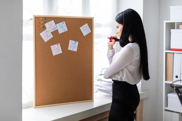 Młoda dziewczyna trzyma w dłoni marker i stoi przy tablicy z naklejkami.