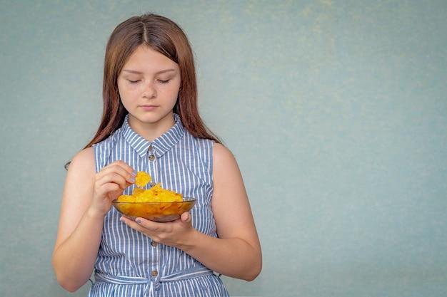 Młoda dziewczyna trzyma w ręku talerz frytek