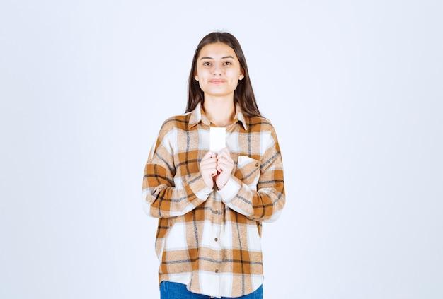 Młoda dziewczyna trzyma wizytówkę na białej ścianie.