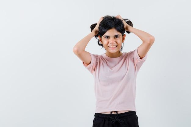 Młoda dziewczyna trzyma włosy obiema rękami w różowy t-shirt i czarne spodnie i wygląda szczęśliwy