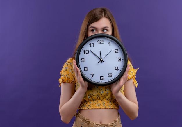 Młoda dziewczyna trzyma zegar i chowając się za nim patrząc na lewą stronę na odosobnionej fioletowej ścianie z miejsca na kopię