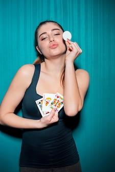 Młoda dziewczyna trzyma żetony i karty do pokera na niebieskim tle studia